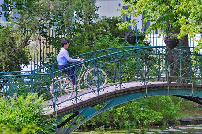 Kvinne på sykkel i Nygårdsparken. Foto: Thomas Morel, AlfGundersen